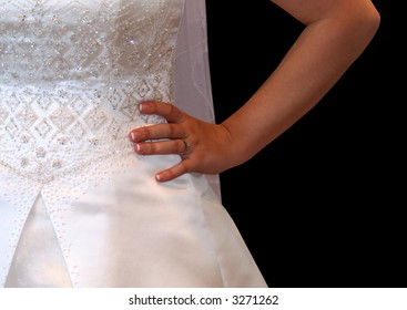 Bride standing with hand on hip in her wedding dress and engagement ring on black background