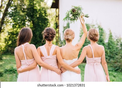 bride standing with her back in a white wedding dress and raised hand with three bridesmaids