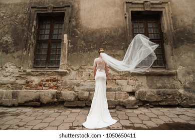 The bride is standing next to the historic house. Bride dress near the old historic facade. Wedding and the historic city.