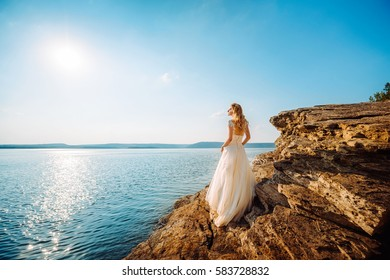 Bride standing on the edge of a cliff and looking at the sea. Sky with clouds and the sea in the background.