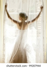 The bride standing on the window behind the curtains