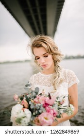 Bride stands with a bouquet of flowers