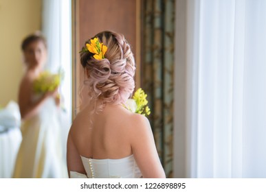 The bride stands with her back to the camera and looks at her reflection in the mirror, the reflection is blurred. Bride in dress with open back