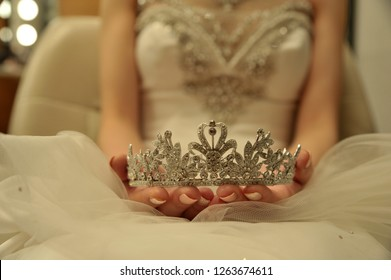 A bride with a tiara in hand