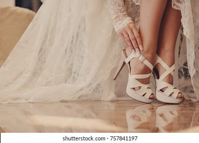 The bride touches her wedding shoes.