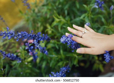 Bride is touching a blue flower