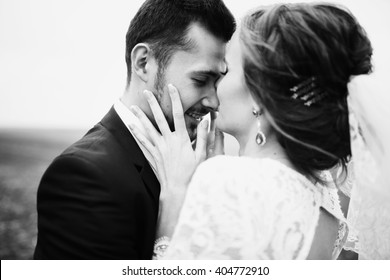 Bride is touching the groom's face tenderly