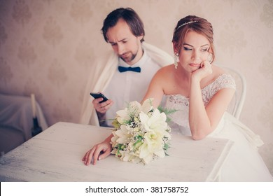 the bride upset the groom is distracted by the phone during a wedding photo session, careless couple