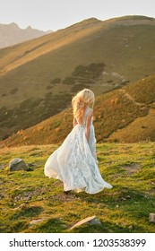 Bride in vintage wedding dress running away at sunset. Spectacular mountain landscape in the background. Travelers love to party. runaway Bride