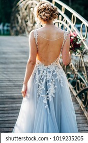 Bride is walking across bridge in grey wedding dress with naked back
