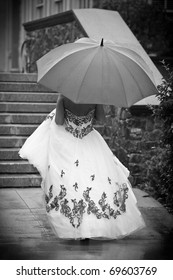 A bride walking away holding an umbrella in black and white