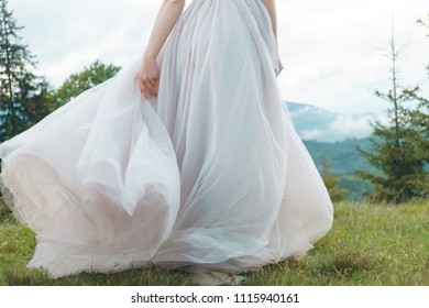bride walking on meadow and holding dress skirt