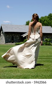 A bride walking outside and wind blowing her dress