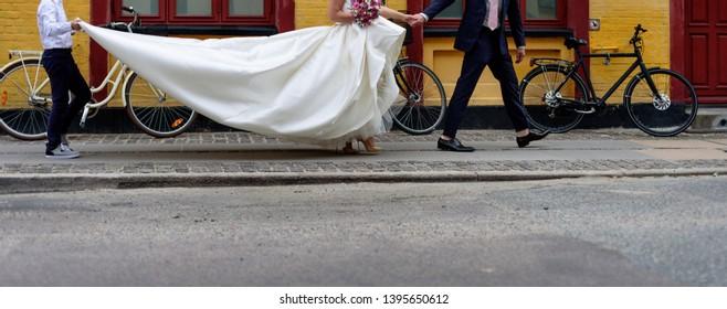 Bride walking a street wearing long classic wedding dress.