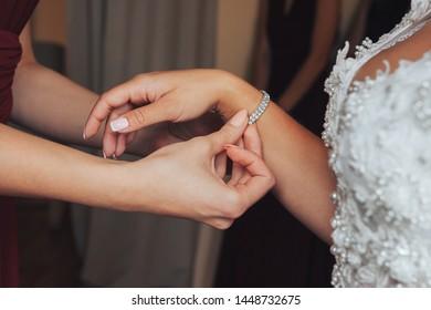 Bride wearing a bracelet. Fees bride. girlfriend helps the bride