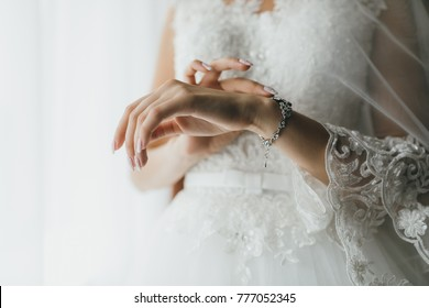 Bride wearing jewelry on hand in the morning on the wedding day.