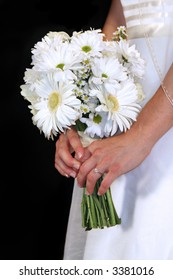 Bride wearing a slightly off-white wedding dress holding a bouquet with her engagement ring and veil showing