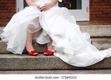 Bride wearing white wedding dress and red shoes