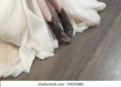 Bride wears brown boots, wooden floor background