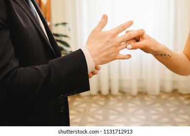 The bride wears a ring for groom