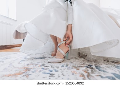 The bride wears wedding shoes while sitting on the bed. Bottom view