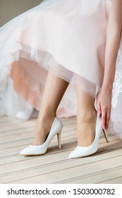 Bride wears white elegant shoes on foot in the wedding day. Close-up shot of  fashion wedding shoes.