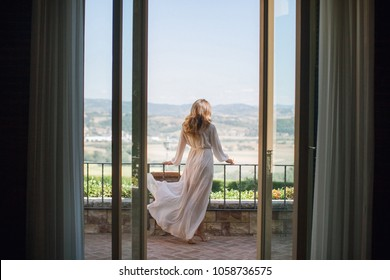 the bride in the wedding boudoir is standing on the balcony and admiring the solar italy