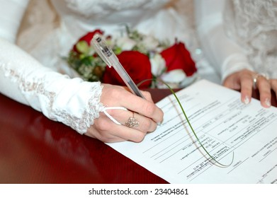 Bride with wedding bunch of flowers (bouquet) signing marriage lines (certificate).