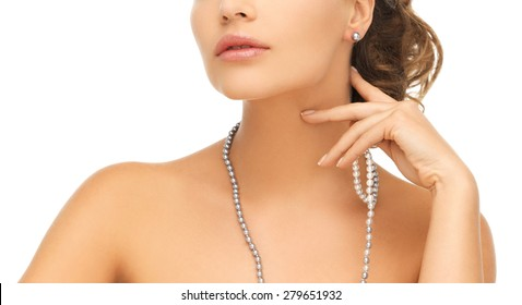 bride and wedding concept - beautiful woman wearing pearl earrings and necklace