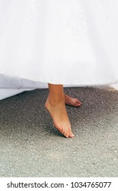 Bride with wedding dress bare feet on the ground