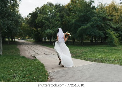 the bride in a wedding dress with a bouquet in a hand cheerfully runs away