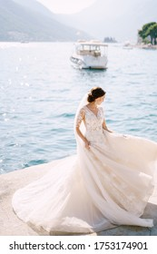 The bride in a wedding dress is dancing on the pier, waving a dress. Fine-art wedding photo in Montenegro, Perast.