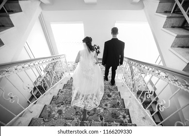 the bride in a wedding dress descends the stairs accompanied by the groom, holds her hand, helping to walk on heels heels on the stairs on the day of the wedding ceremony the couple together love