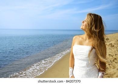 A bride in wedding dress in golden sunshine on a beach