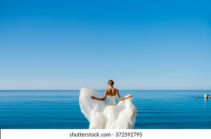 the bride in a wedding dress on sea background