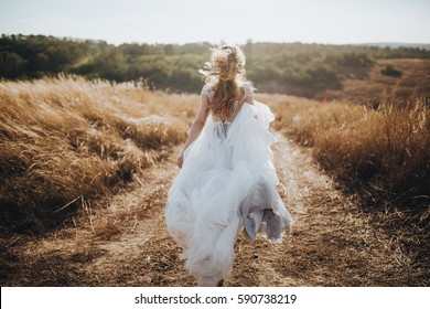 Bride in wedding dress running in a field on the road at sunset
