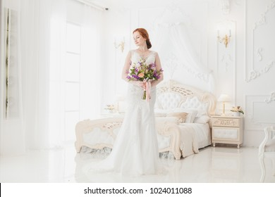 Bride in the wedding dress is standing in the royal bedroom, she is waiting for her fiance.