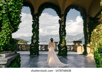 Bride in a wedding dress stands on a beautiful balcony overlooking mountains and lake