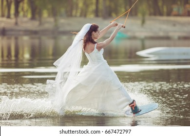 Bride in a wedding dress and veil on her head is engaged in extreme sports, she is on a wakeboard.