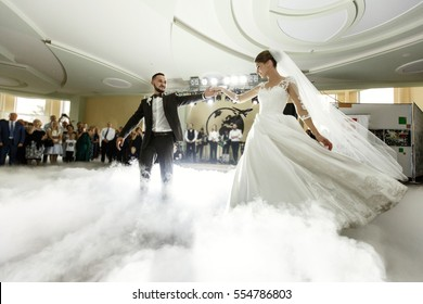 Bride whirls to groom dancing with him in the smoke