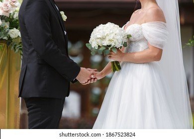 bride in white dress with  beautiful bouquet of wight roses and groom on the wedding ceremony. just married couple. happy Newlyweds holding hands close up . Wedding day. beautiful just married couple