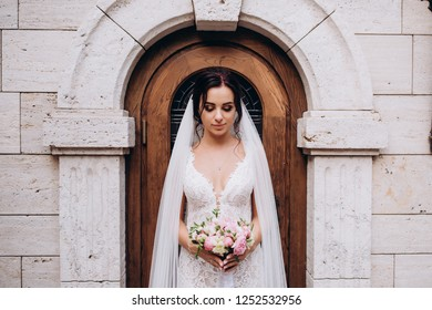 Bride in a white dress. Bride with a bouquet at the door of the castle.