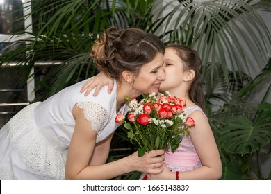 A bride in a white dress with a bouquet of flowers embraces her daughter in a pink dress against a background of green plants