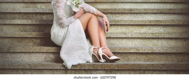 Bride in a white dress with a bouquet sits on the stairs.