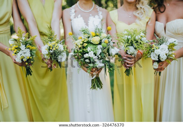 bride in a white dress and bridesmaids dresses are yellow and are holding bouquets of yellow flowers and greenery