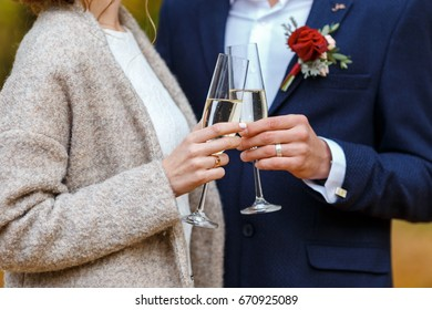 Bride in white dress and coat and groom in blue suit hold in their hands wineglasses with champagne and hugging. Wedding celebration