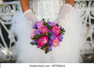 Bride in white dress and gloves holding wedding bouquet made of pink peonies