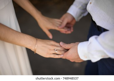 Bride in white dress and groom in white shirt each other's hands with wedding rings