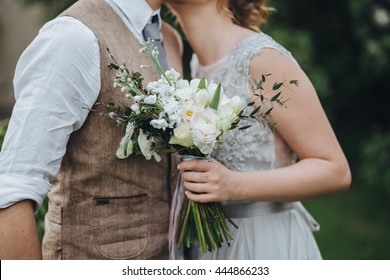 The bride in a white dress and groom in a waistcoat standing in the green garden, and holding a wedding bouquet