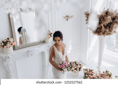 A bride in a white dress is holding a beautiful wedding bouquet. The bride is waiting for the groom in the white room.